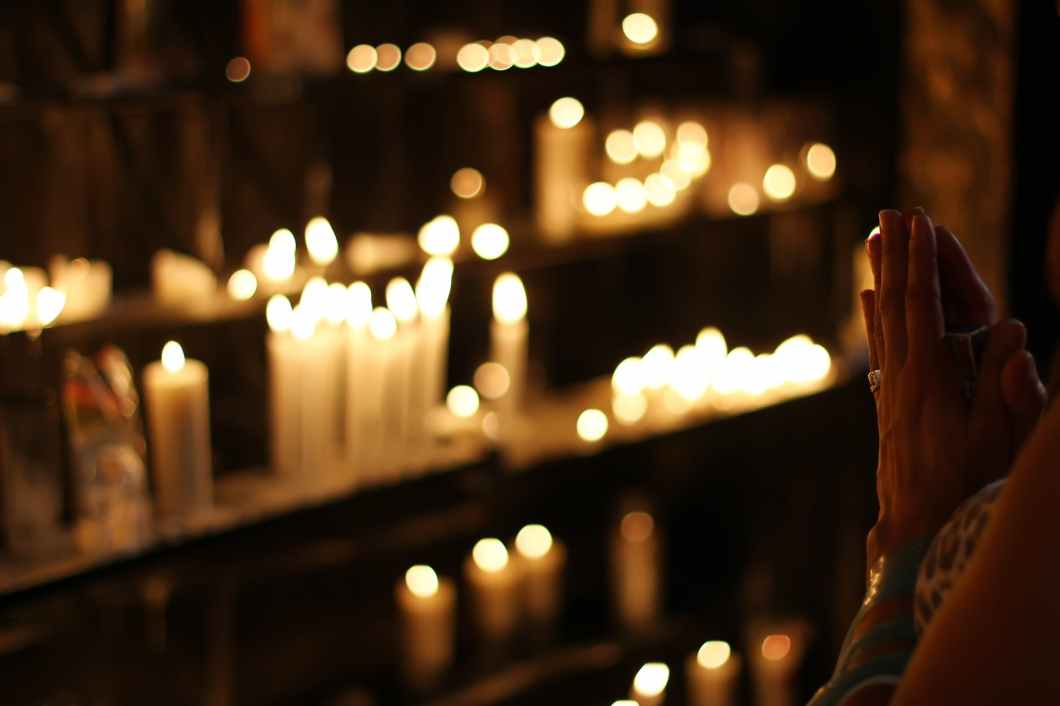 close up photograph of person praying in front lined candles